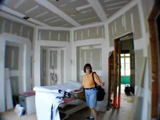 """Fisheye lens view of Audra Frank working at a large installation""."